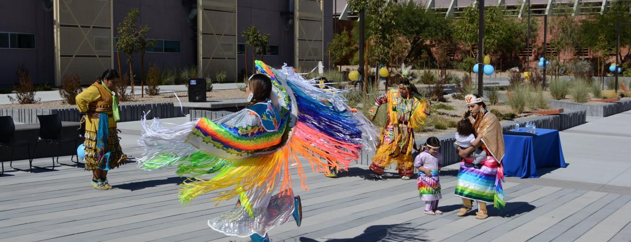 Native American performers dancing in traditional garments