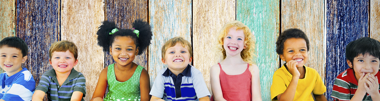 seven toddlers smiling for a picture in front of a fence
