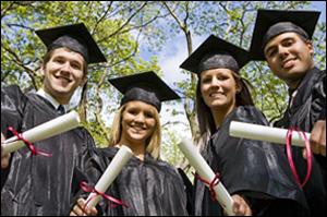 Students holding diplomas at graduation.