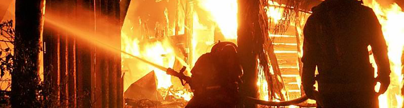 Two firefighters inside a burning building using their fire hose to battle the fire