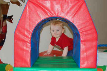 child in red shirt peeking out of tent