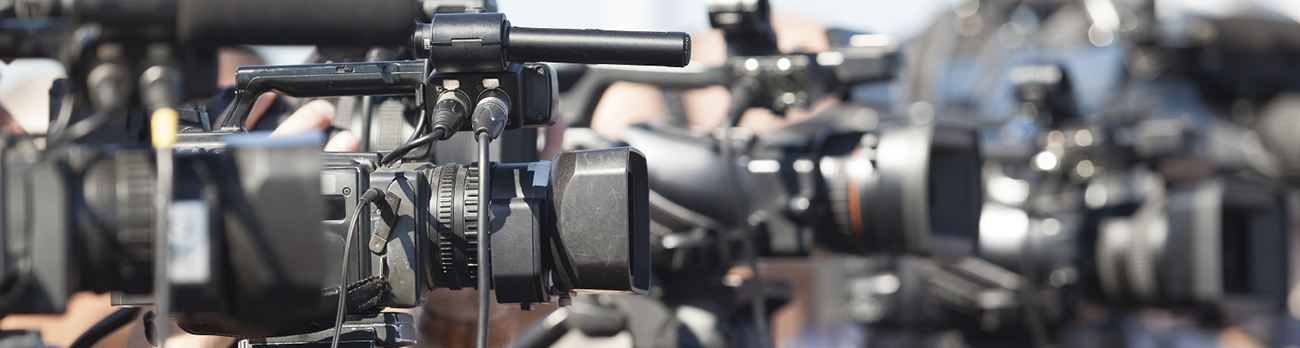 Close up view of a video camera sitting on a tripod