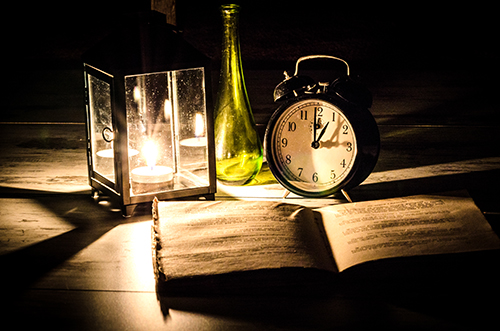 Image of clock and lamp, and book in the dark