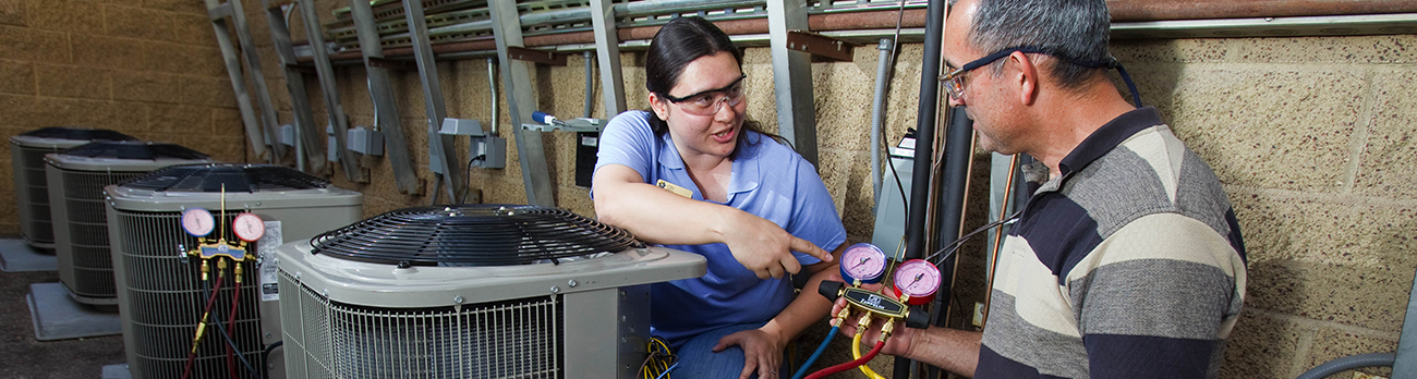 Man and Woman reviewing AC System Pressure Gauge