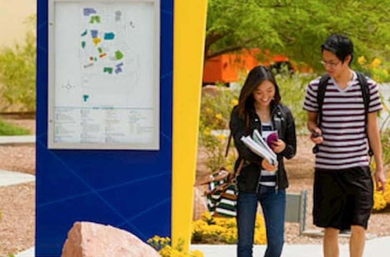 Students walking past the campus directory map