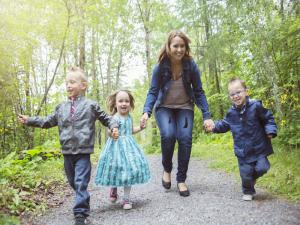 Three toddlers finger walking with staff