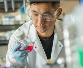 Scientist looking at bottle of fluid