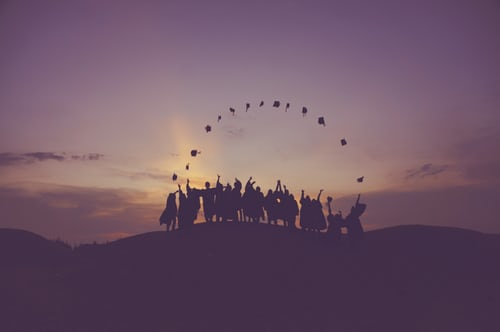 Graduating students throwing graduation caps in the air at sunset