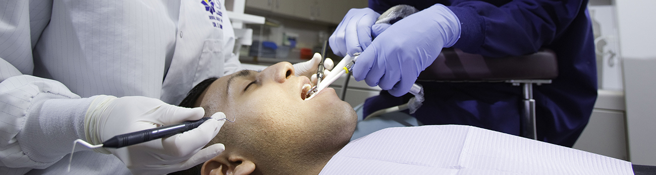 Patient sitting in a dental chair receiving a tooth exam