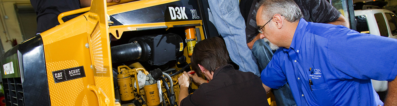 Instructor and student working on a heavy construction, tractor engine