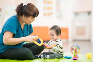 student playing with infant child